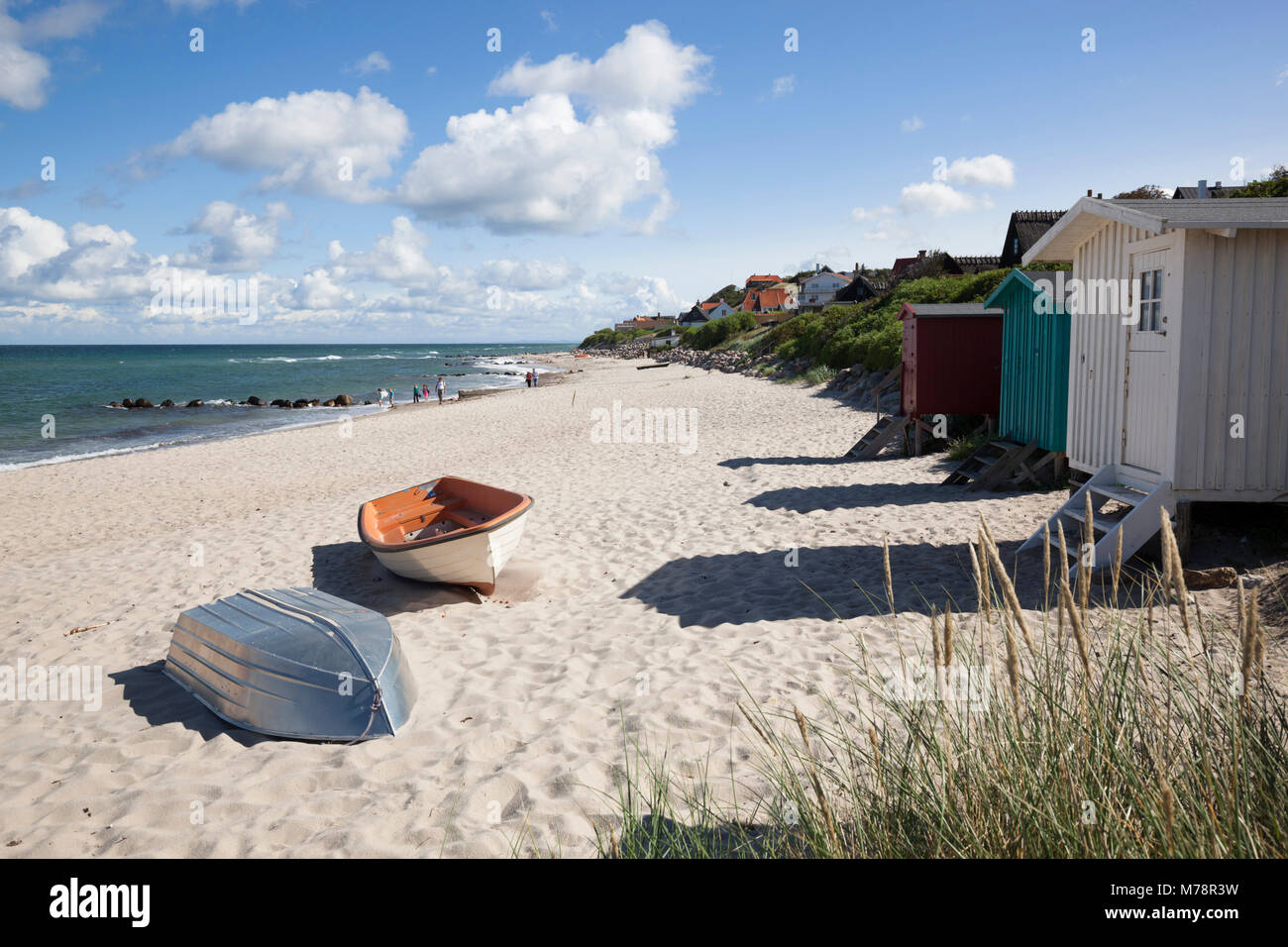Boats and beach huts on white sand beach with town behind, Tisvilde, Kattegat Coast, Zealand, Denmark, Scandinavia, - Stock Image
