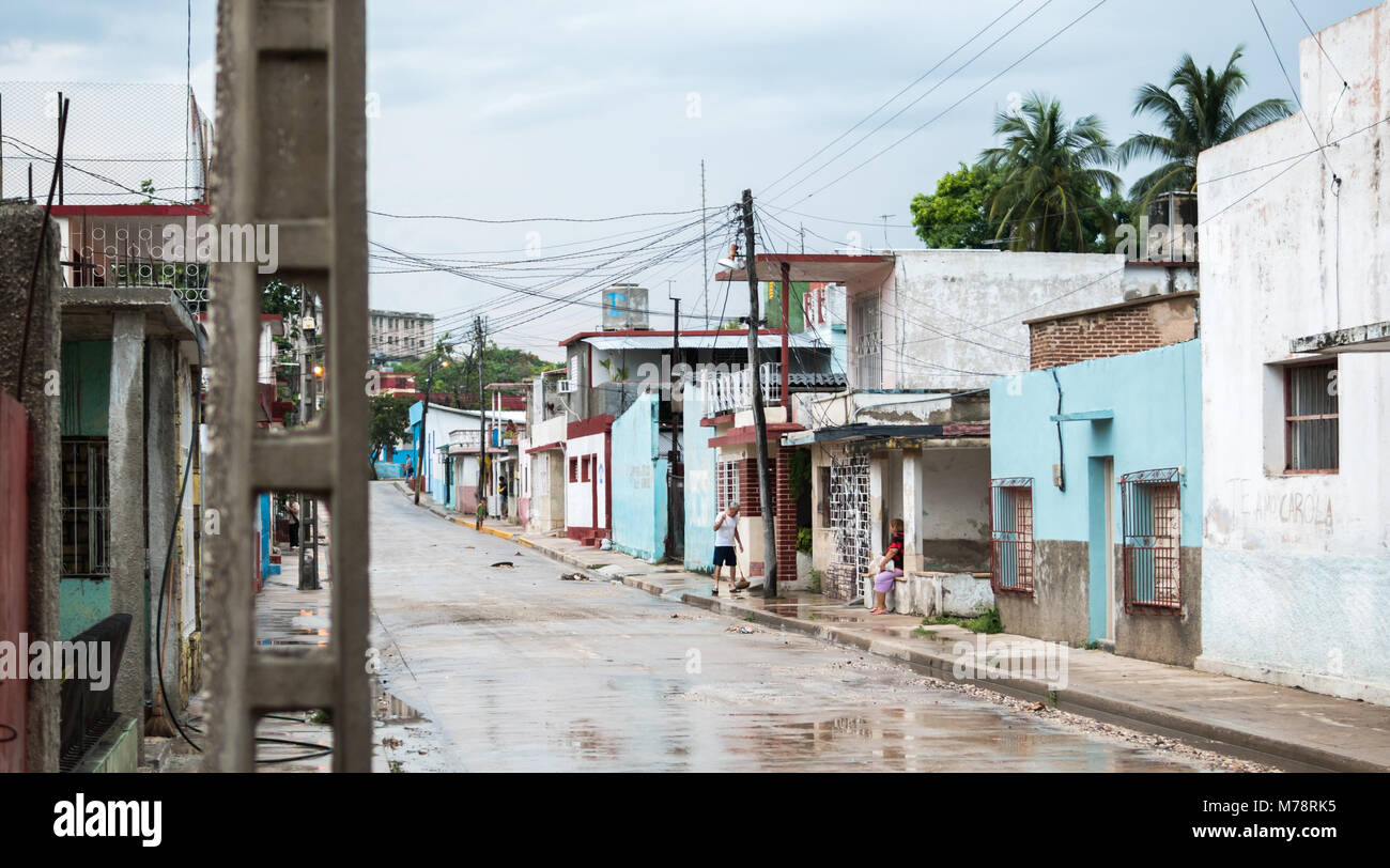Holguin, Cuba - August 31, 2017: A man cleans the sidewalk in front of a home after a rainstorm. Stock Photo