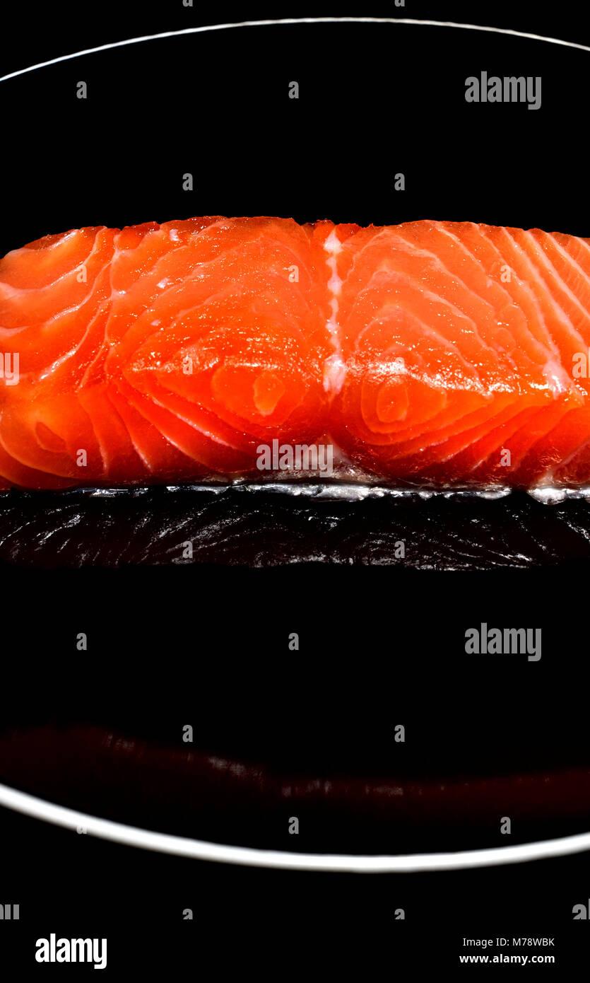 Raw Salmon steak / fillet on a black plate - Stock Image