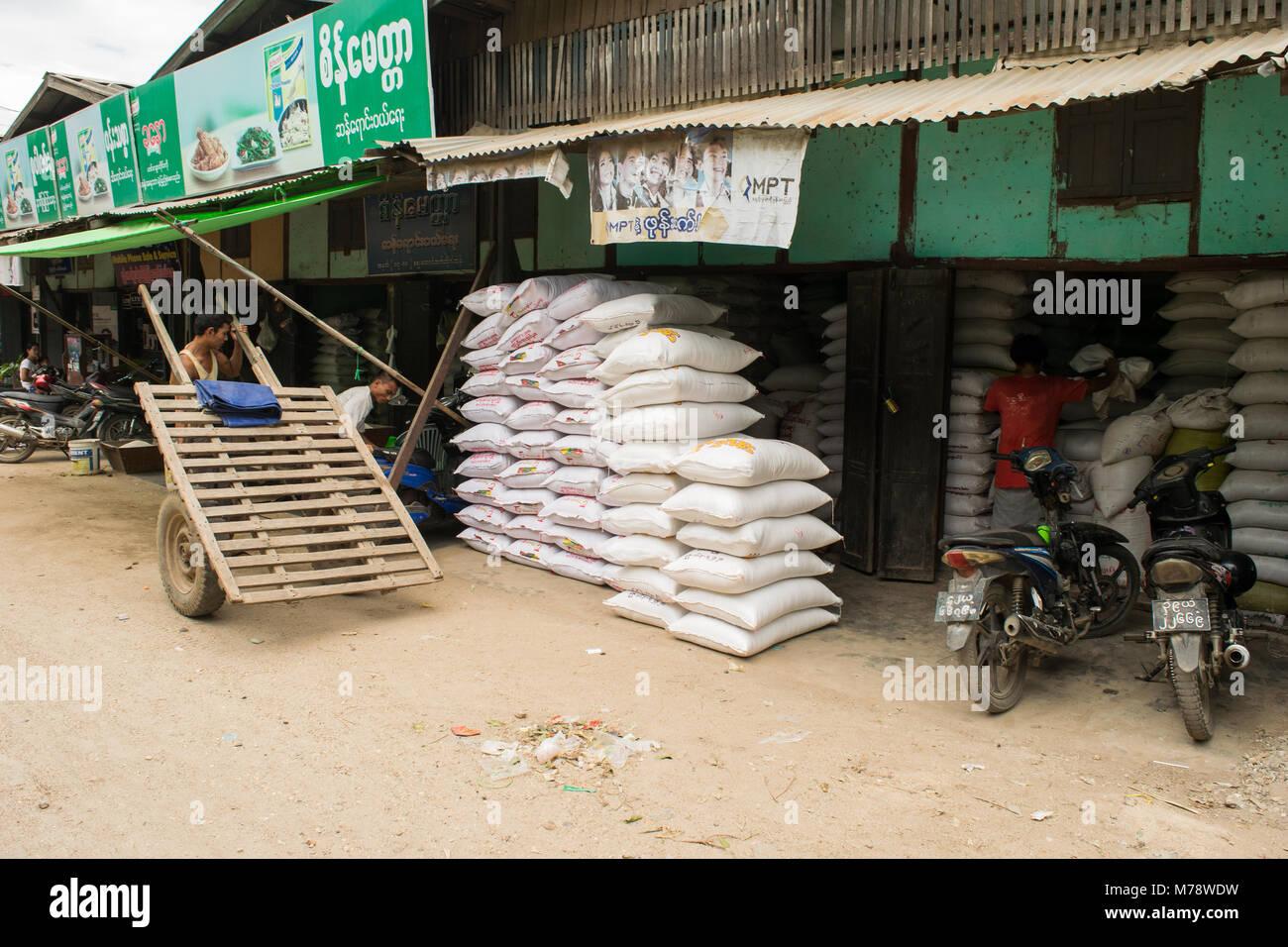 A vendor at Nyaung U market selling sacks of rice or flour. Burmese man with makeshift wooden cart with car tires - Stock Image