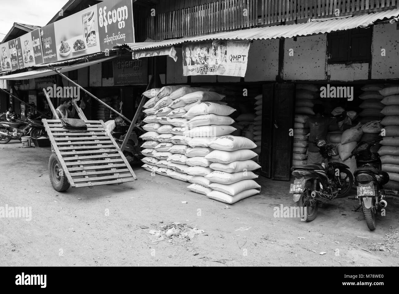 A vendor at Nyaung U market selling sacks of rice or flour. Burmese man with makeshift wooden cart with car tires - Stock Image