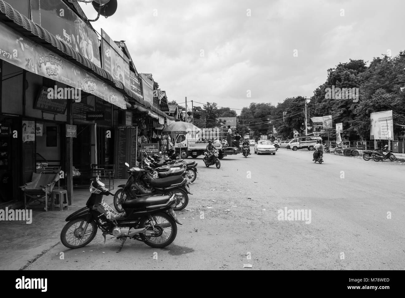 A sandy road next to Nyaung U market near Bagan, Myanmar, Burma. market stalls and parked motorcycles, common mode - Stock Image