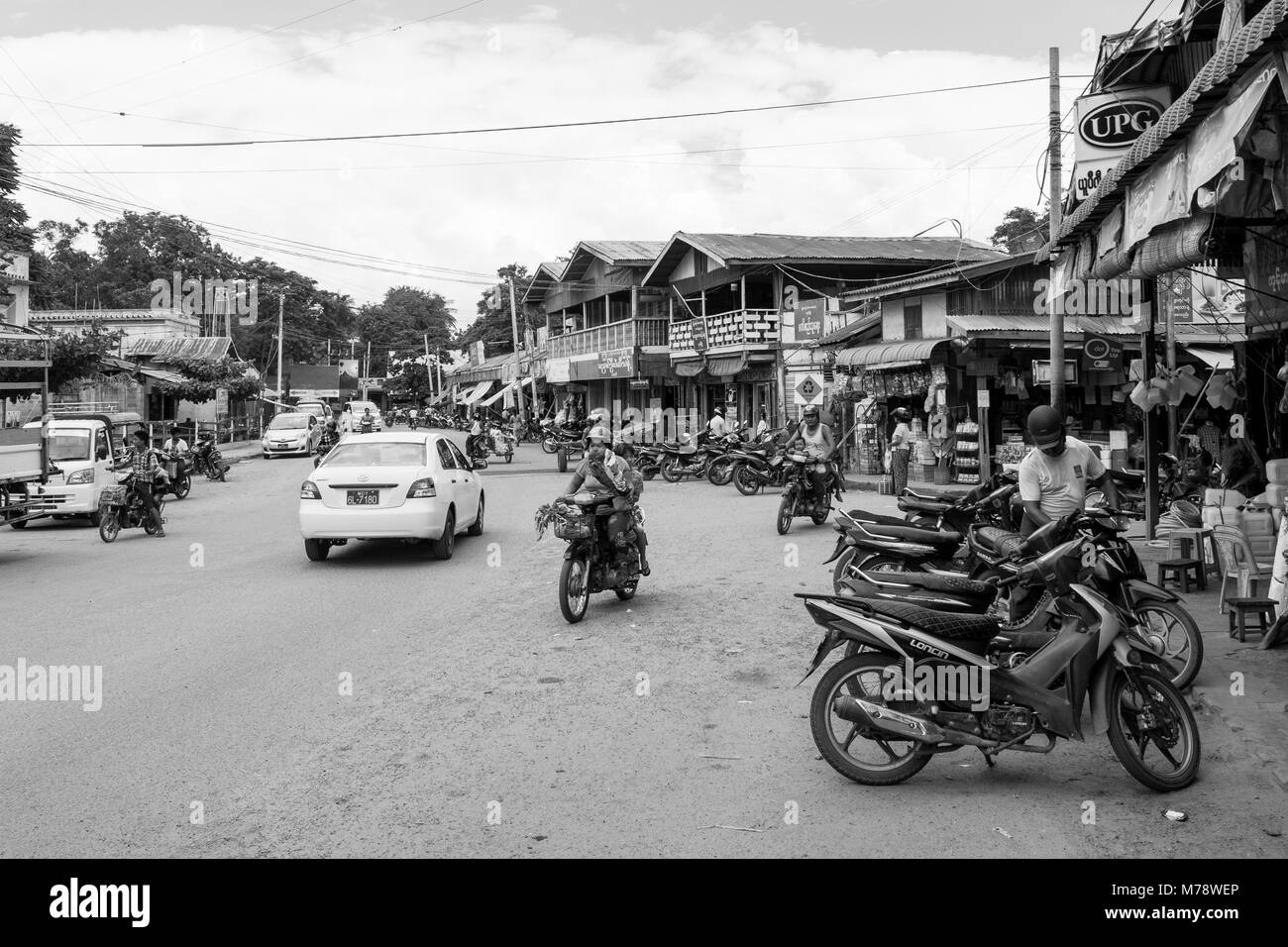 A sandy road next to Nyaung U market near Bagan, Myanmar, Burma. market stalls and parked motorcycles, common mode - Stock Image