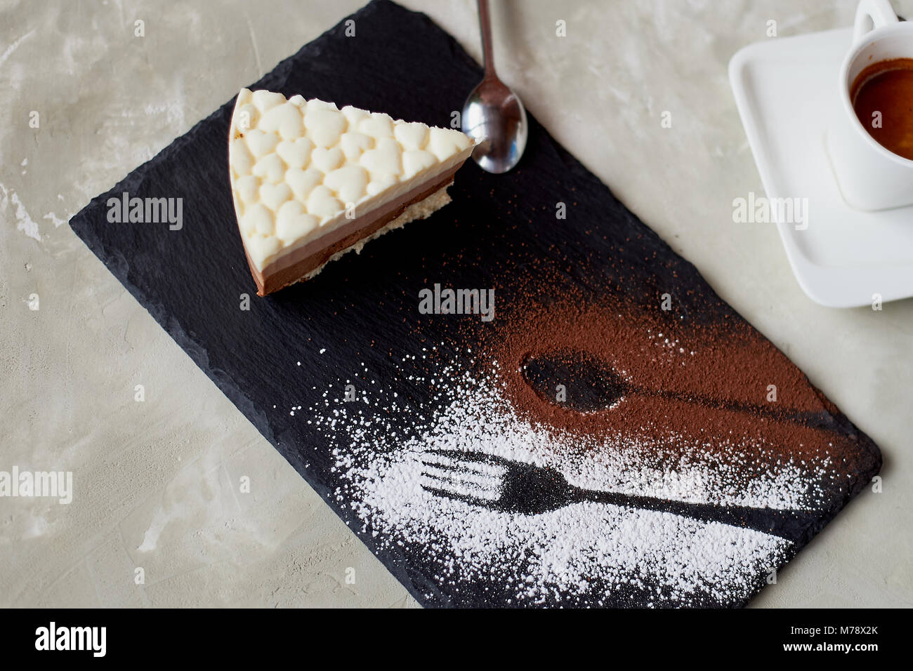 The outline of the fork and spoon , sprinkled with cocoa powder. Three chocolate cake on a stone stand and coffe Stock Photo