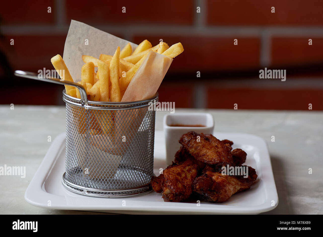 Chicken wings with sauce ketchup and fries in a metal stand on parchment paper - Stock Image