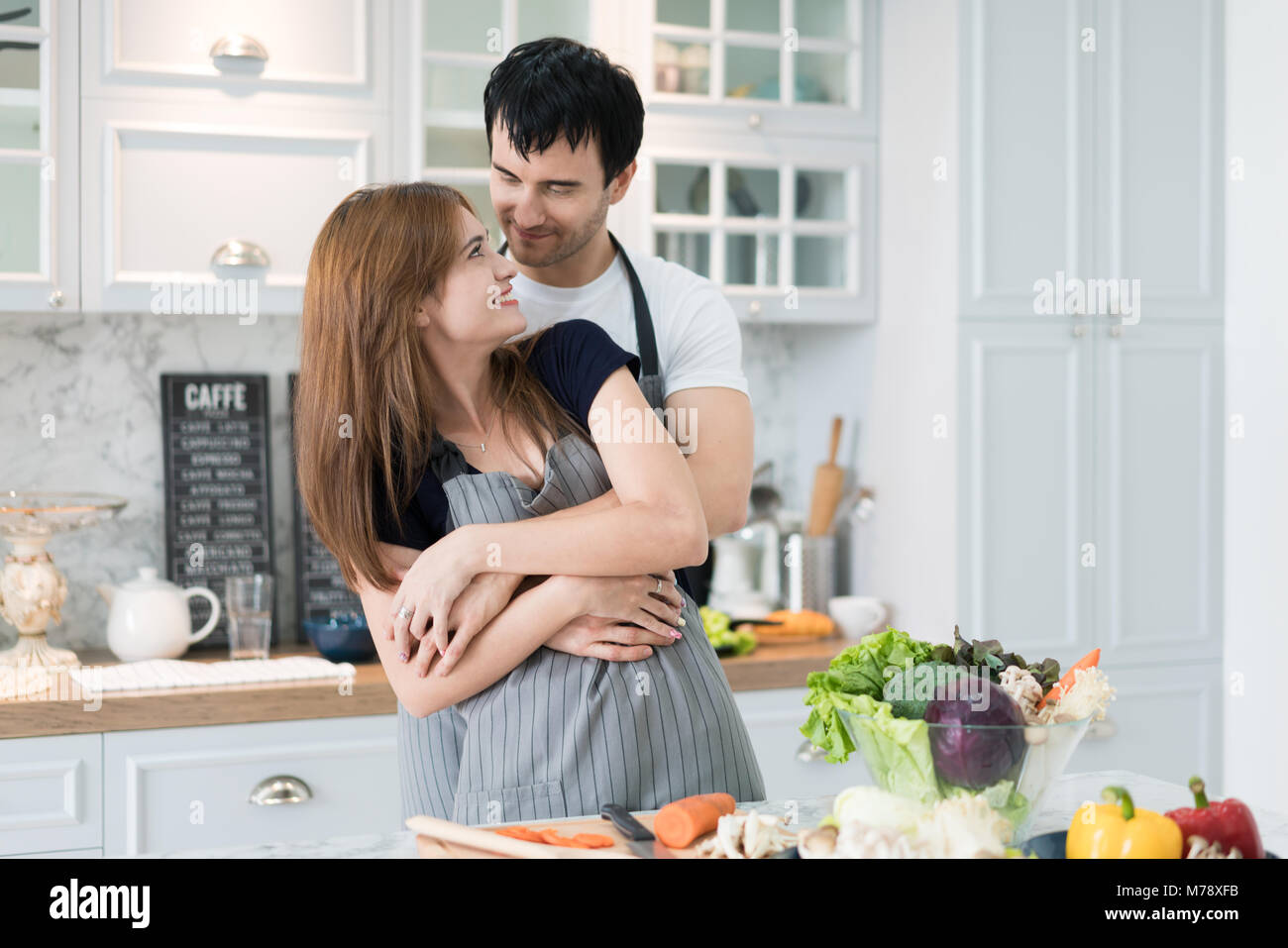 Lovely young couple preparing healthy meal in the modern kitchen. Man hugging woman romantic in morning at kitchen. Stock Photo
