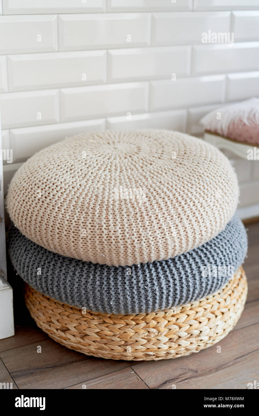 A pile of poufs by the fireplace, one of the rattan and two knitted wool.Cozy location - Stock Image