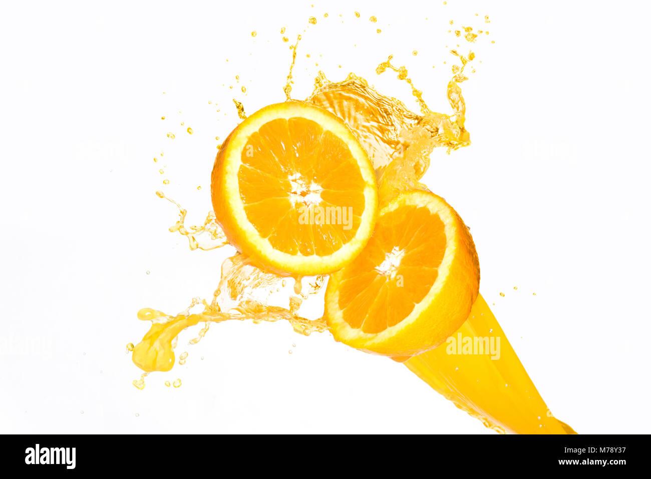 Orange juice splashing on half oranges against a white background - Stock Image