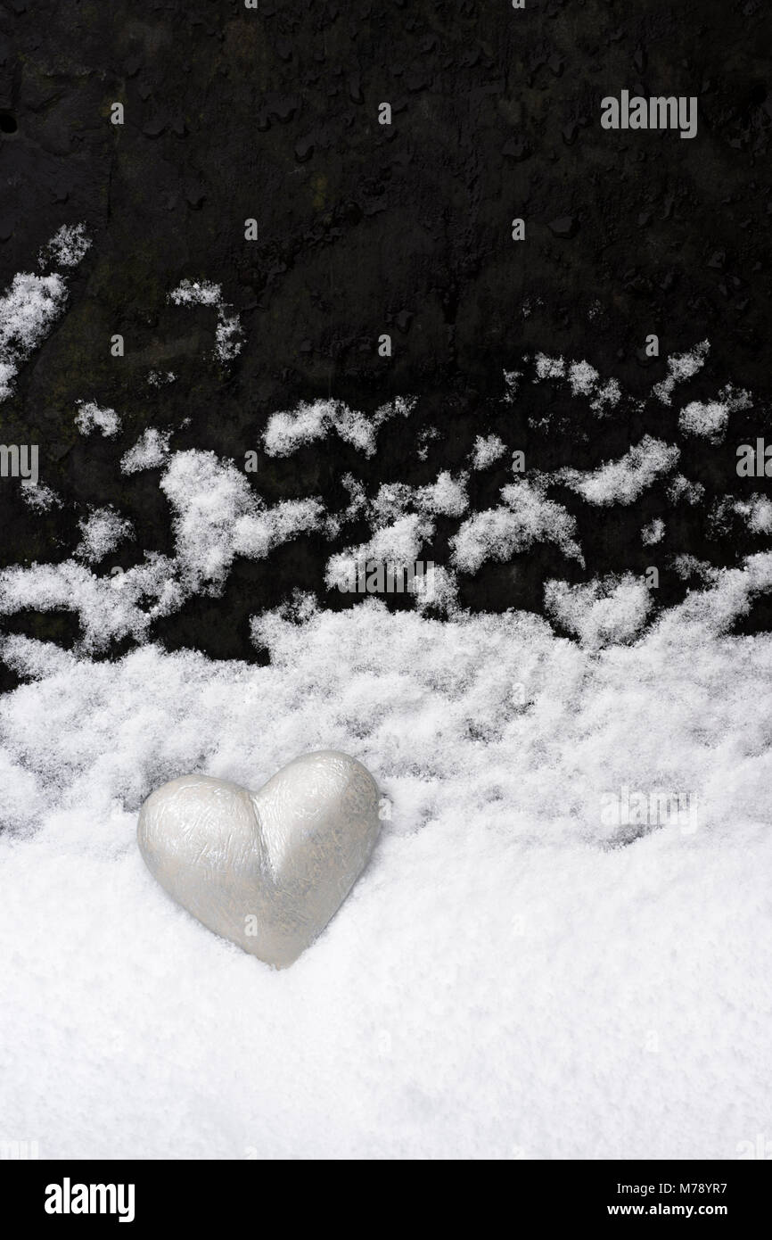 Silver grey painted heart placed against roofing slate upon which snow has settled. A landscape in minature mimicking - Stock Image