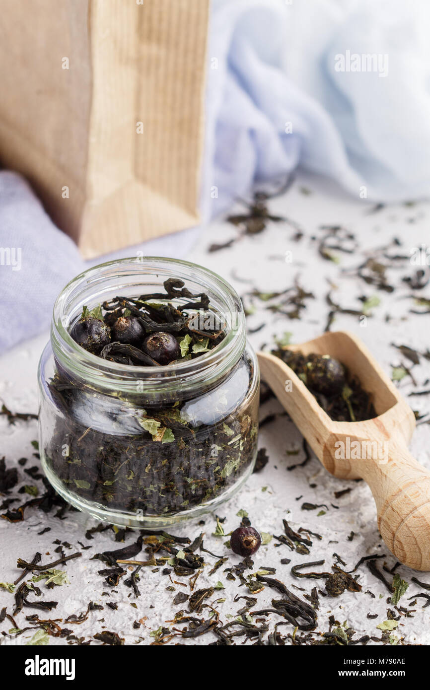 Healthy herbal tea with black currants in a glass jar and wooden scoop. Vitamin drink. Diet. Antioxidant. Selective - Stock Image