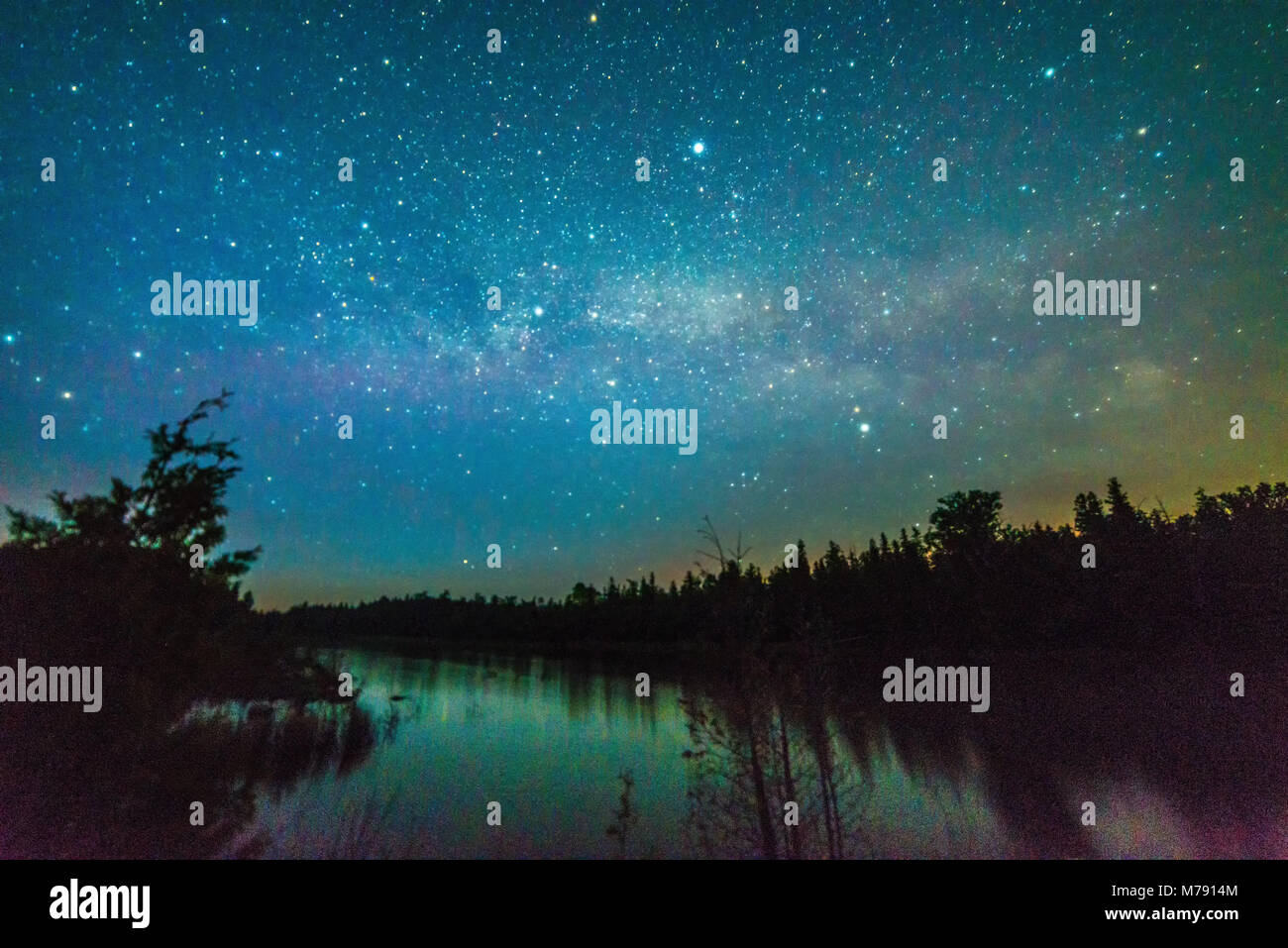 Small lake reflecting with stars and milky way  at night near Lake Huron, Bruce Peninsula, Ontario - Stock Image