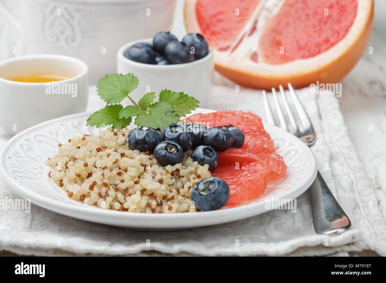 Quinoa porridge with grapefruit, fresh berries blueberry and honey. Healthy and tasty Breakfast. Selective focus - Stock Image