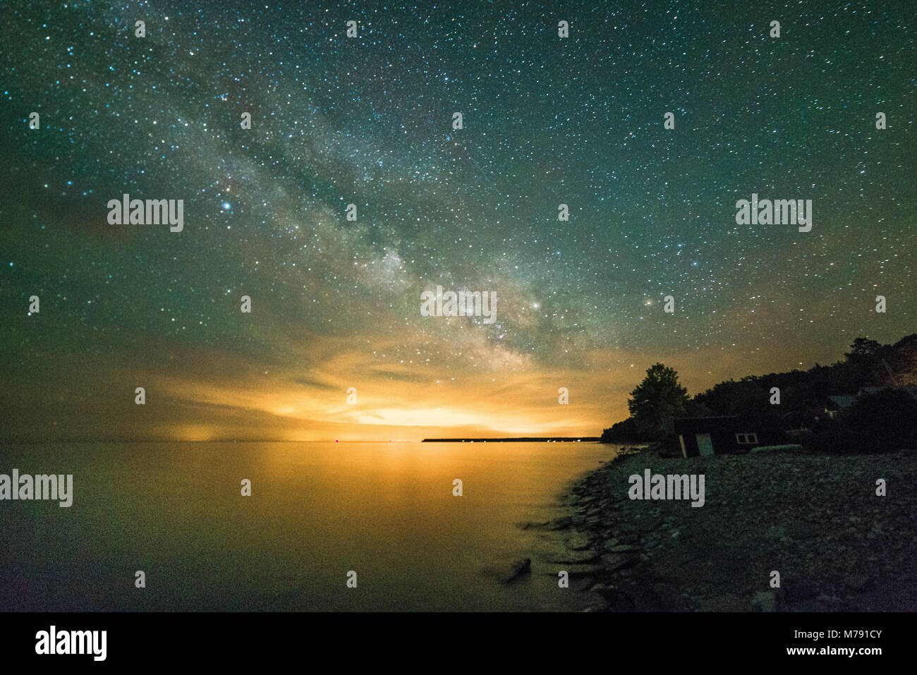 Milky Way and stars over the lake (Georgian Bay part of Lake huron) showing shoreline and cliffs in the summer - Stock Image