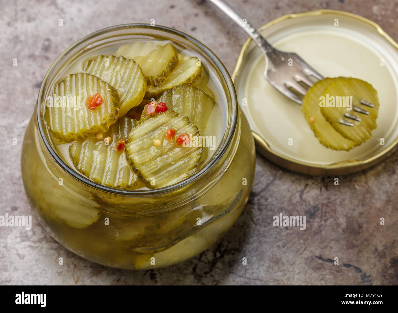 Slices of pickled cucumbers with pepper and mustard in a jar. Snack for gourmets. Selective focus - Stock Image