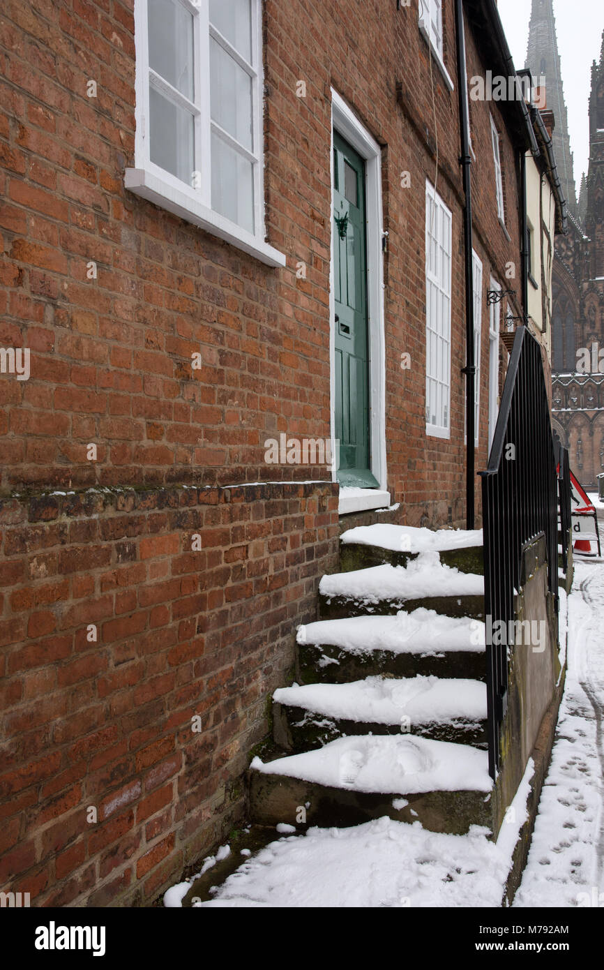 Snow covered steps with metal hand rails to a house in The Close Lichfield Staffordshire England - Stock Image