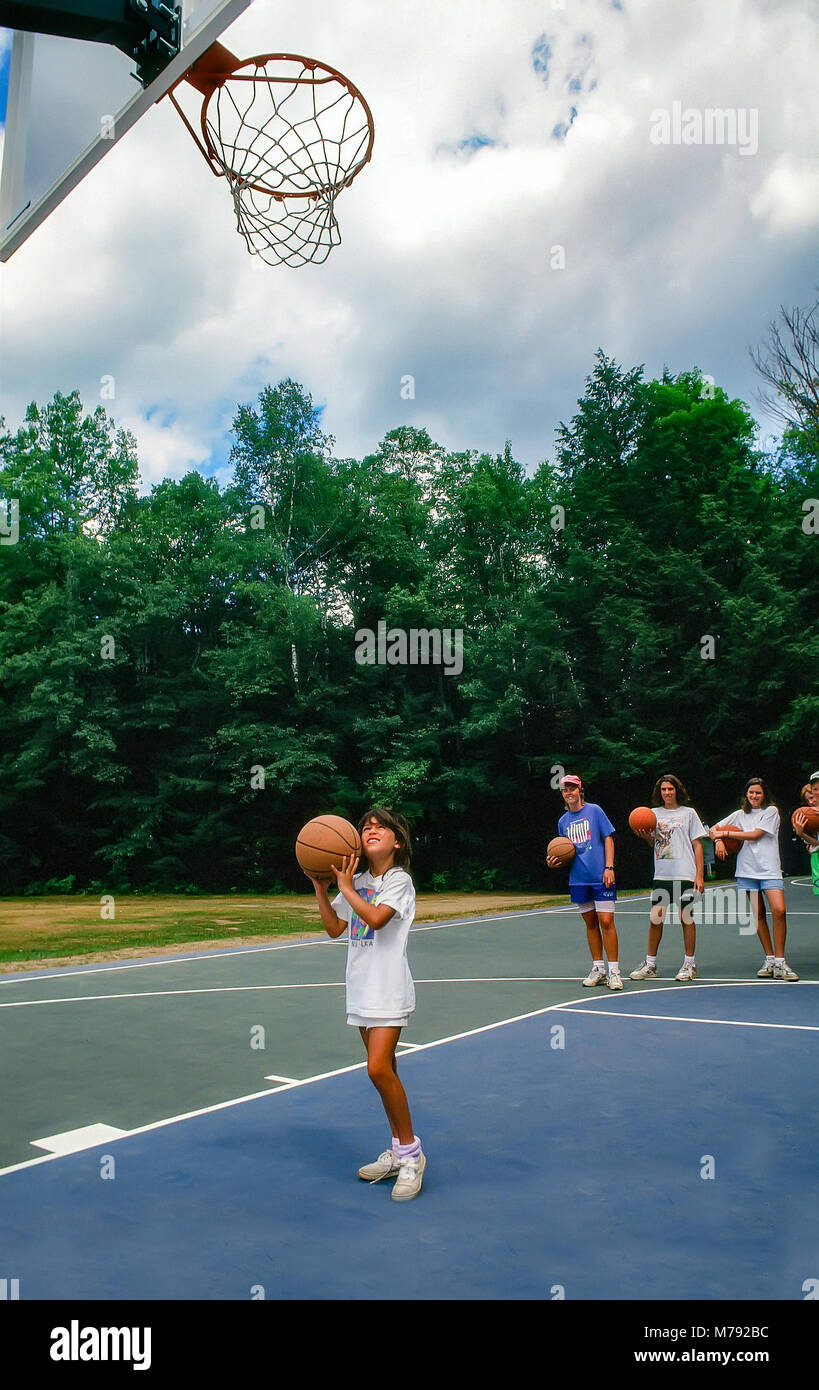A young girl tries to shoot a basketball hoop at summer camp in Vermont, United States, North America. - Stock Image