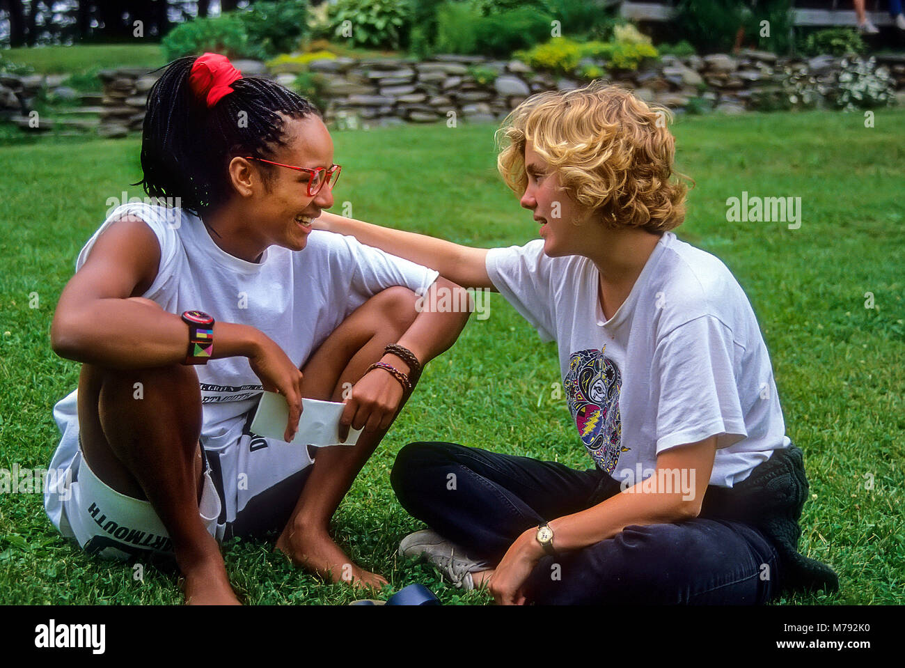 A white and black girl sit together sharing a friendly relationship at summer camp in Vermont, United States, North - Stock Image