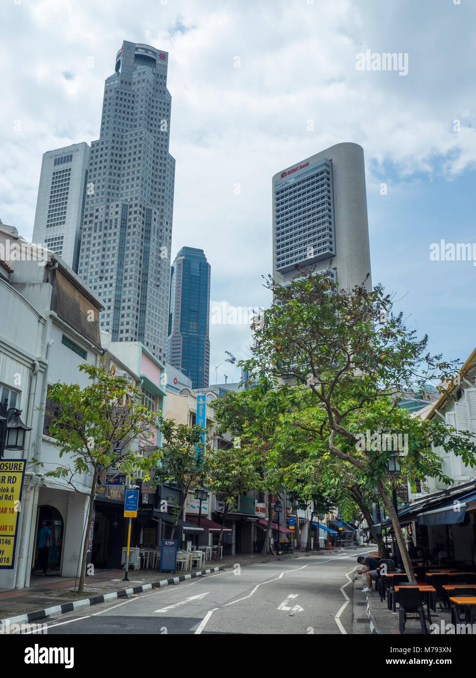 Tree lined Circular Road, and its row of traditional shophouses contrasting with the skyscrapers of downtown Singapore. - Stock Image