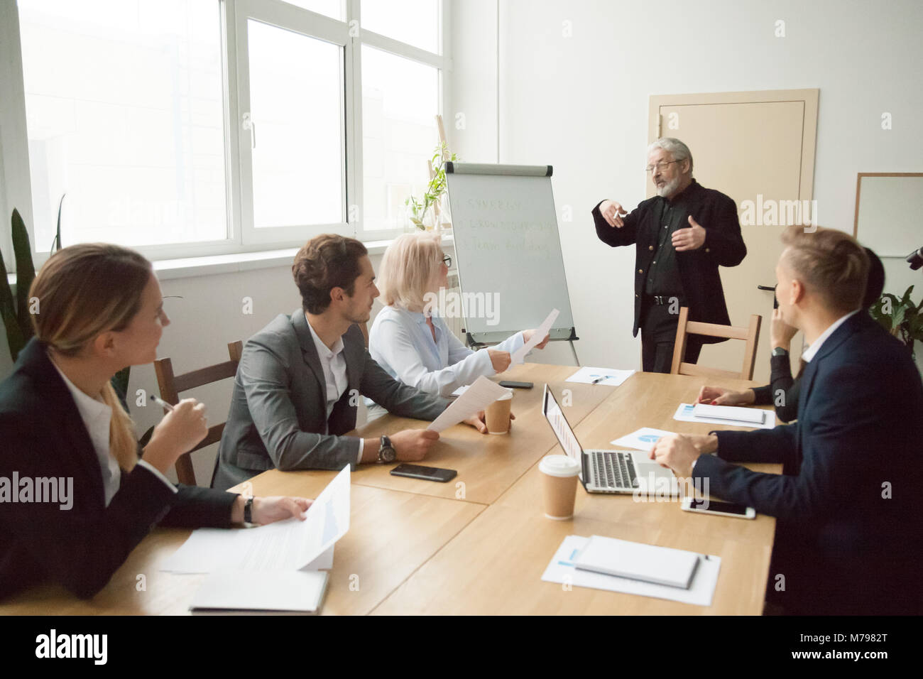 Senior coach giving presentation to executive managers team in b - Stock Image
