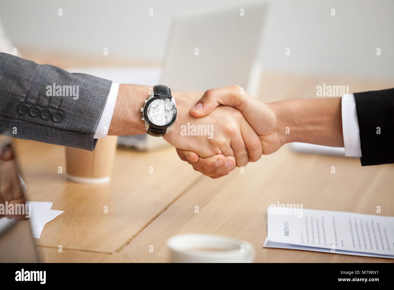 Closeup view of handshake, two businessmen in suits shaking hand - Stock Image