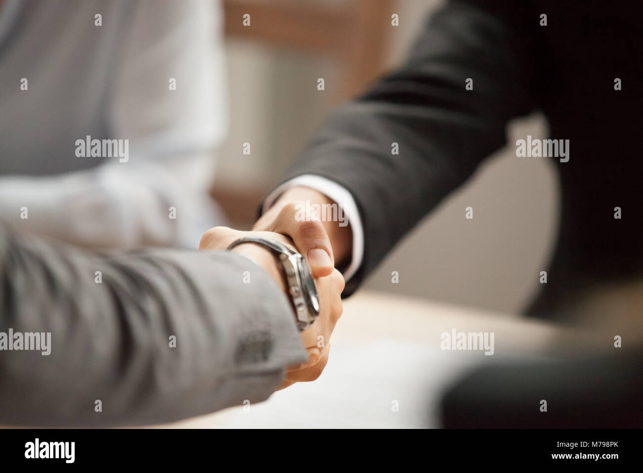 Two businessmen in suits shaking hands at meeting, close up - Stock Image