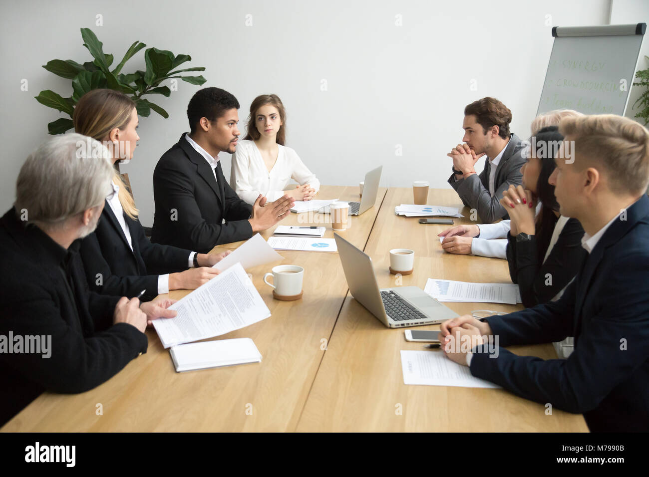 Focused black team leader talking to colleagues at group meeting - Stock Image