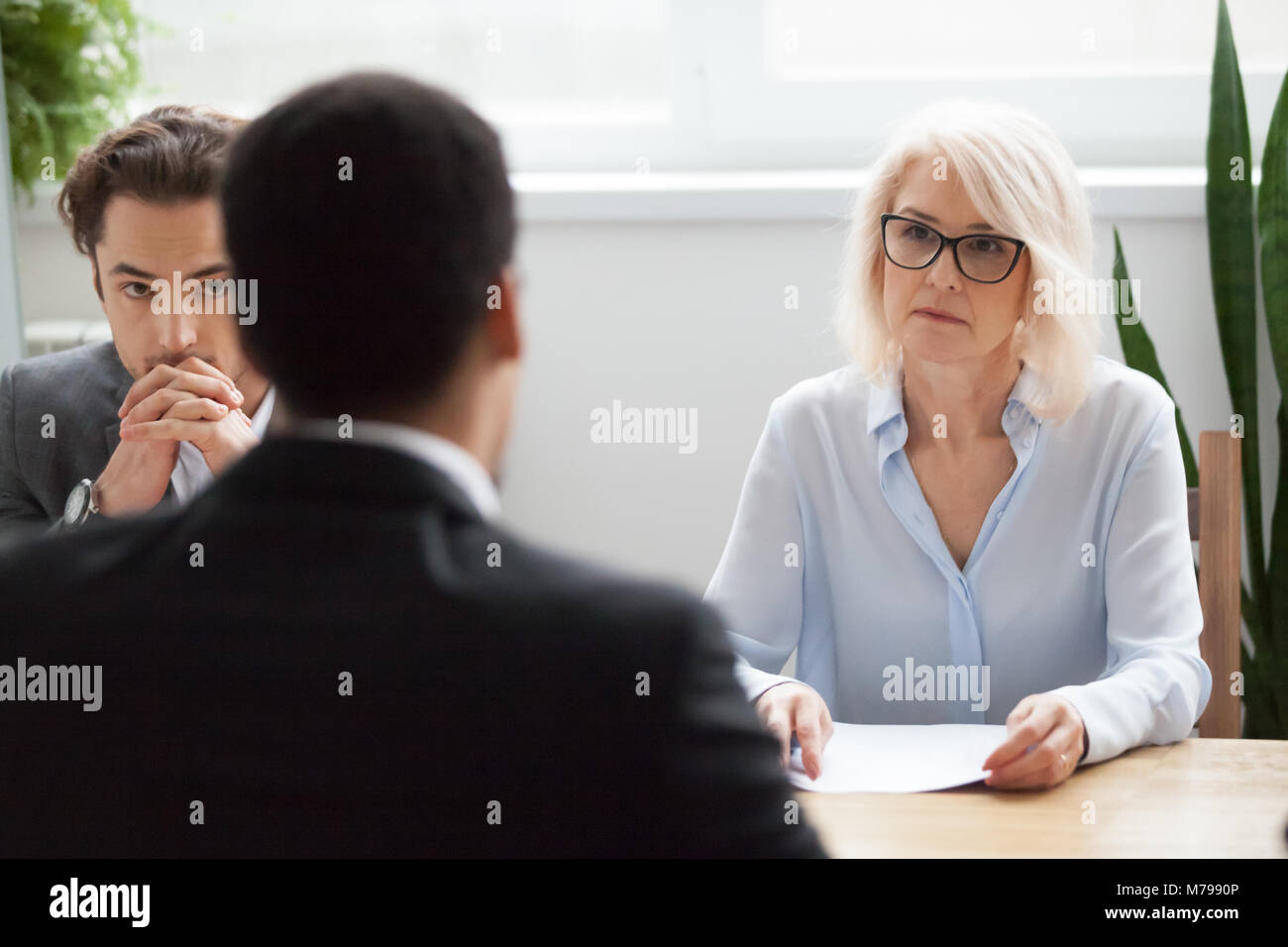 Serious attentive senior hr listening to candidate at job interv - Stock Image