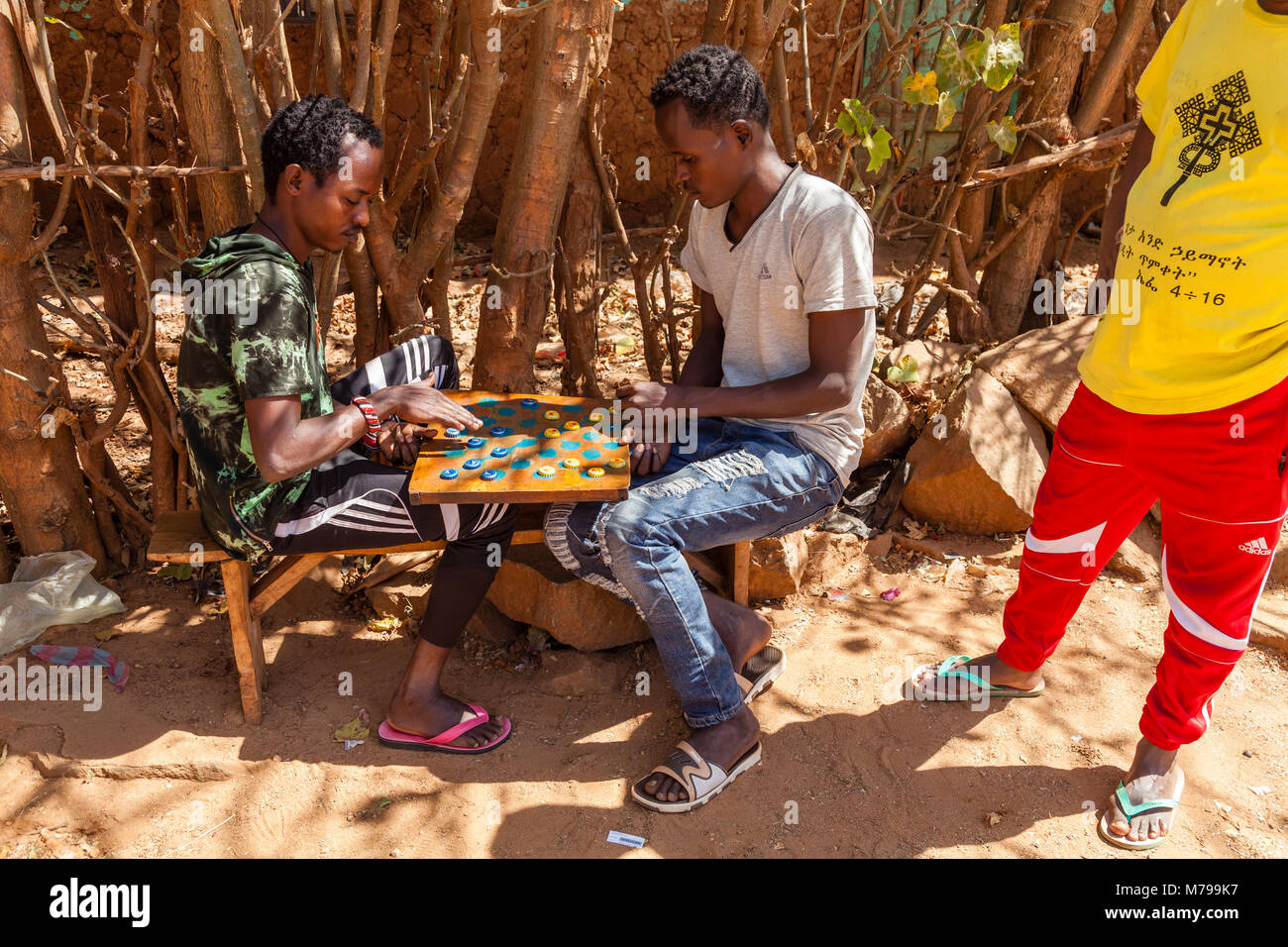Two Young Men Play Draughts (Checkers) Using Bottle Tops, Dimeka, Omo Valley, Ethiopia - Stock Image