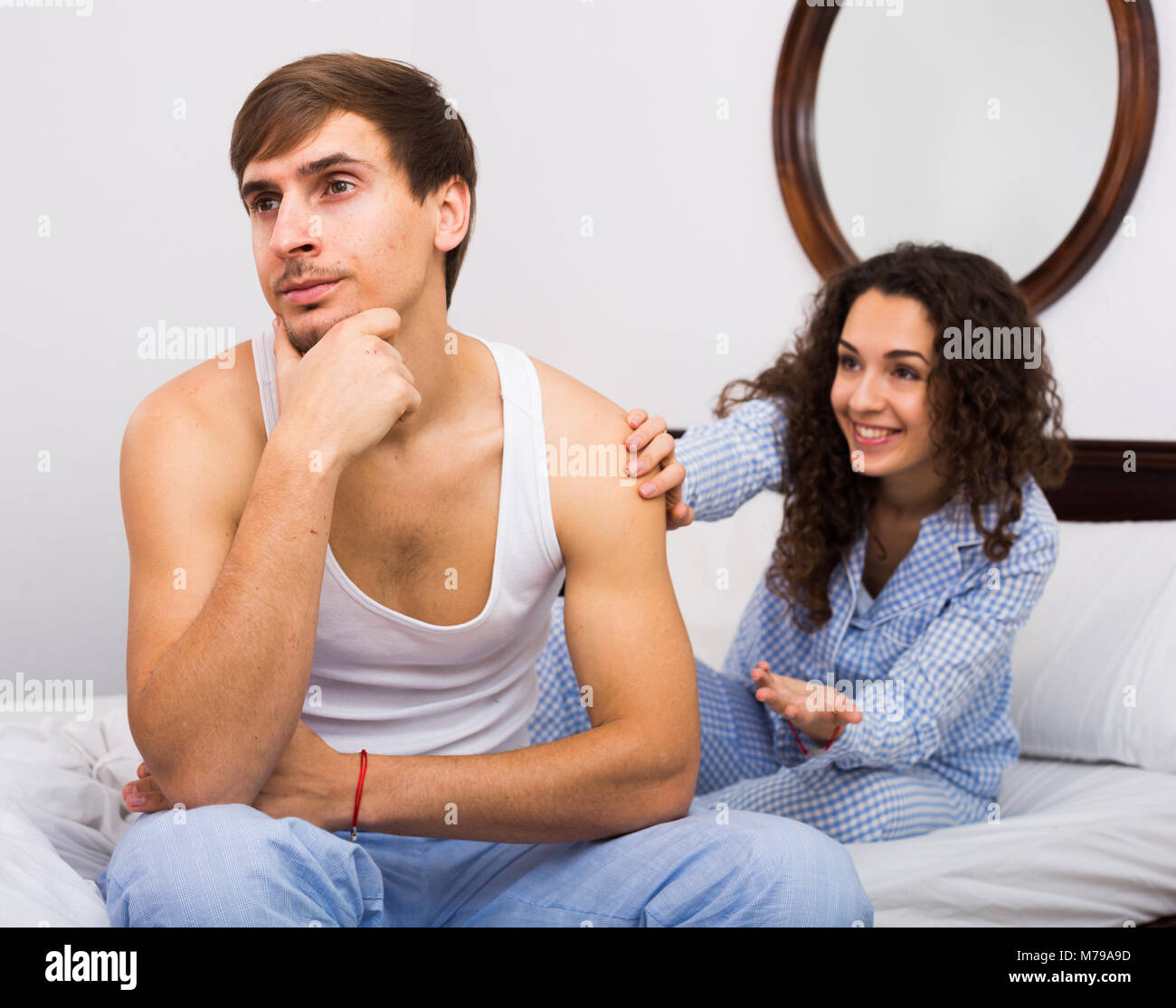Brunette girl wheedling to offended young man sitting in bed - Stock Image