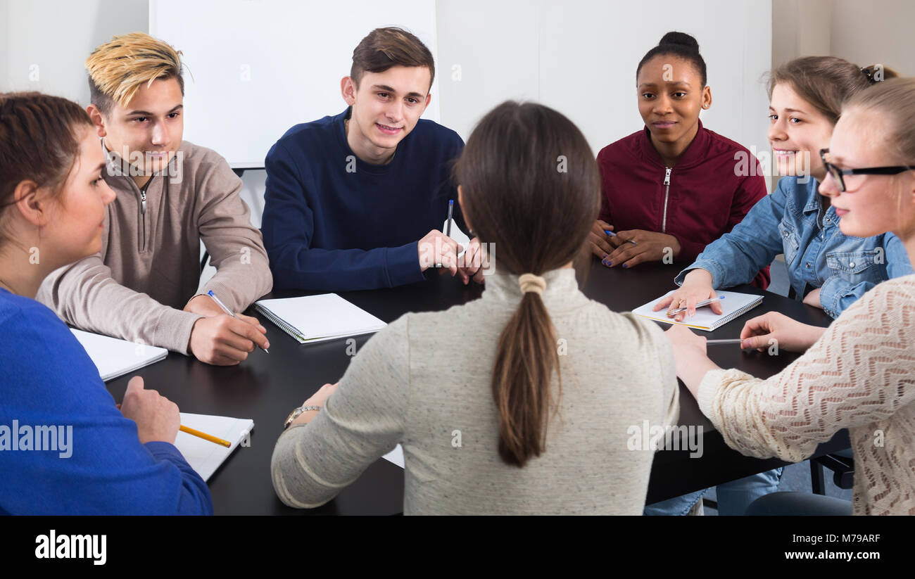 thoughtful classmates having difficult project to complete during class sits by the table - Stock Image