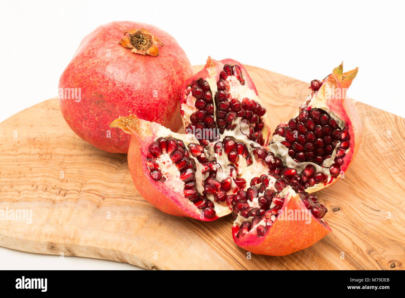 A pomegranate-Punica granatum-bought from a supermarket opened and showing the seeds. Photographed on a white background. - Stock Image