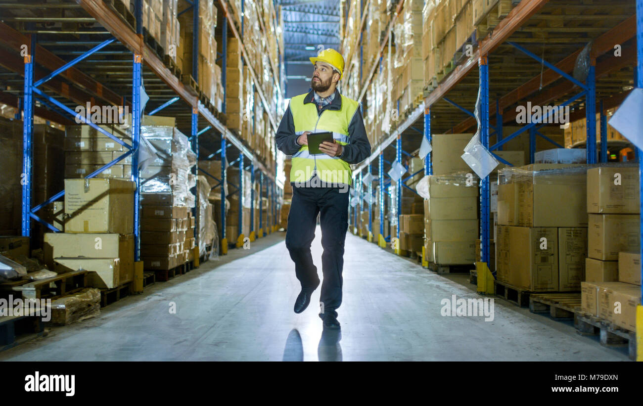 Auditor Wearing Hard Hat with Tablet Computer Counts Merchandise in Warehouse. He Walks Through Rows of Storage - Stock Image