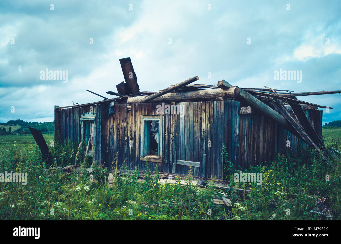 Close-up old ruined wooden rural house is standing among fields. - Stock Image