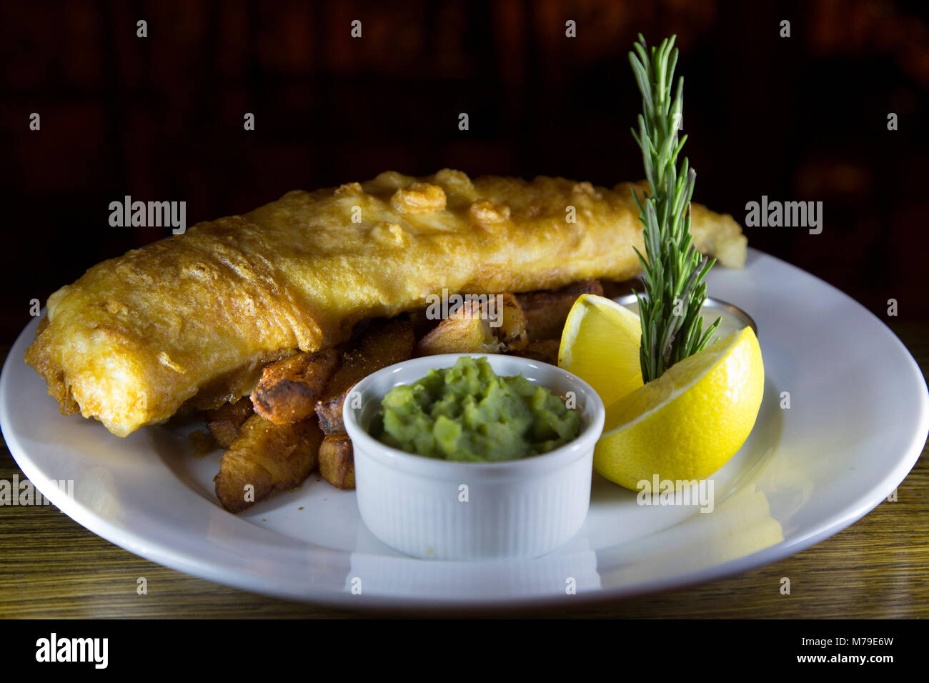 Fish and chips served on a plate in Sunderland, England. The dish is served with a bowl of mushy peas and a piece - Stock Image