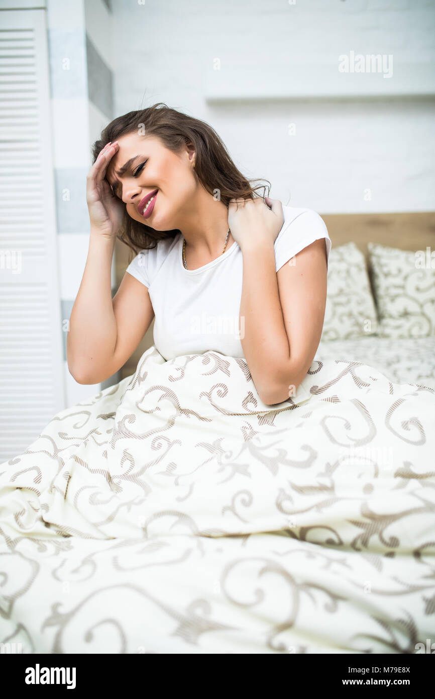 Young Woman Suffering From Neck Pain Sitting On Bed - Stock Image