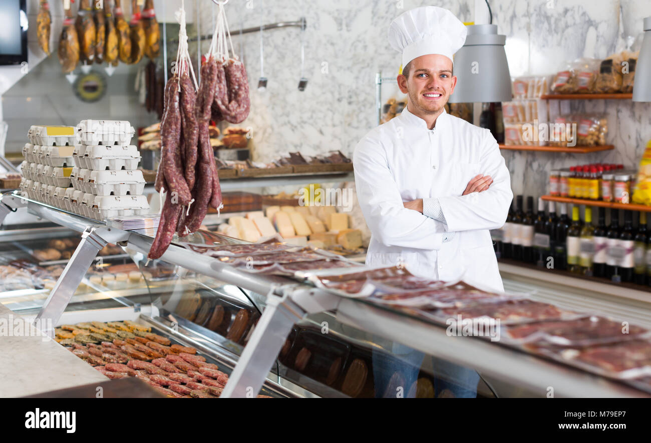 Happy ordinary male seller working at meat market - Stock Image