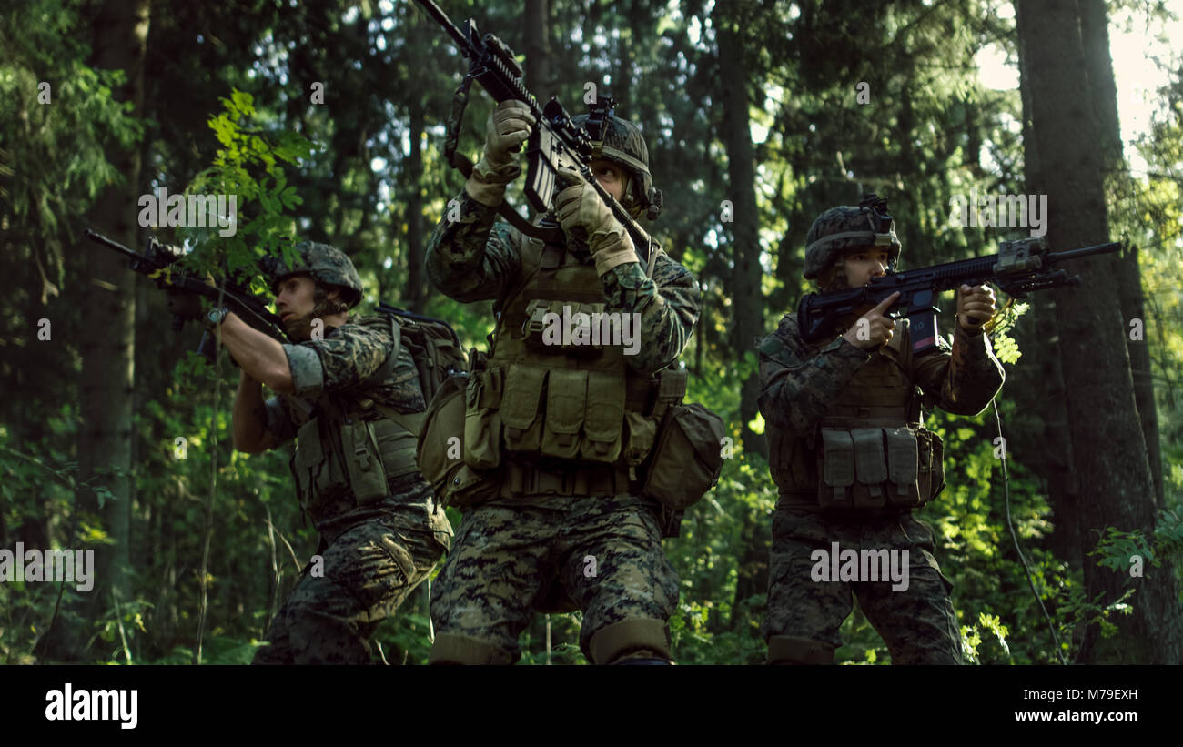 Three Fully Equipped Soldiers Wearing Camouflage Uniform Attacking Enemy, They're in Shooting Ready Stance, - Stock Image