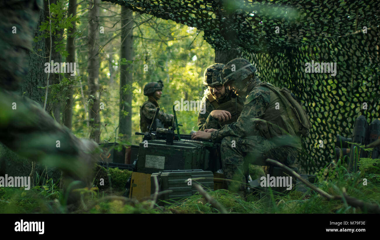 Military Staging Base, Officer Gives Orders to Signalman, They Use Radio and Army Grade Laptop. They're in Camouflaged - Stock Image