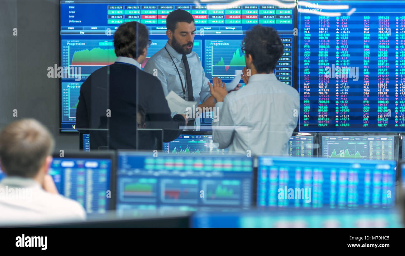 Three Experienced Stock Traders Talking Business, Consulting Documents and Argue About Data. They Work for a Big - Stock Image