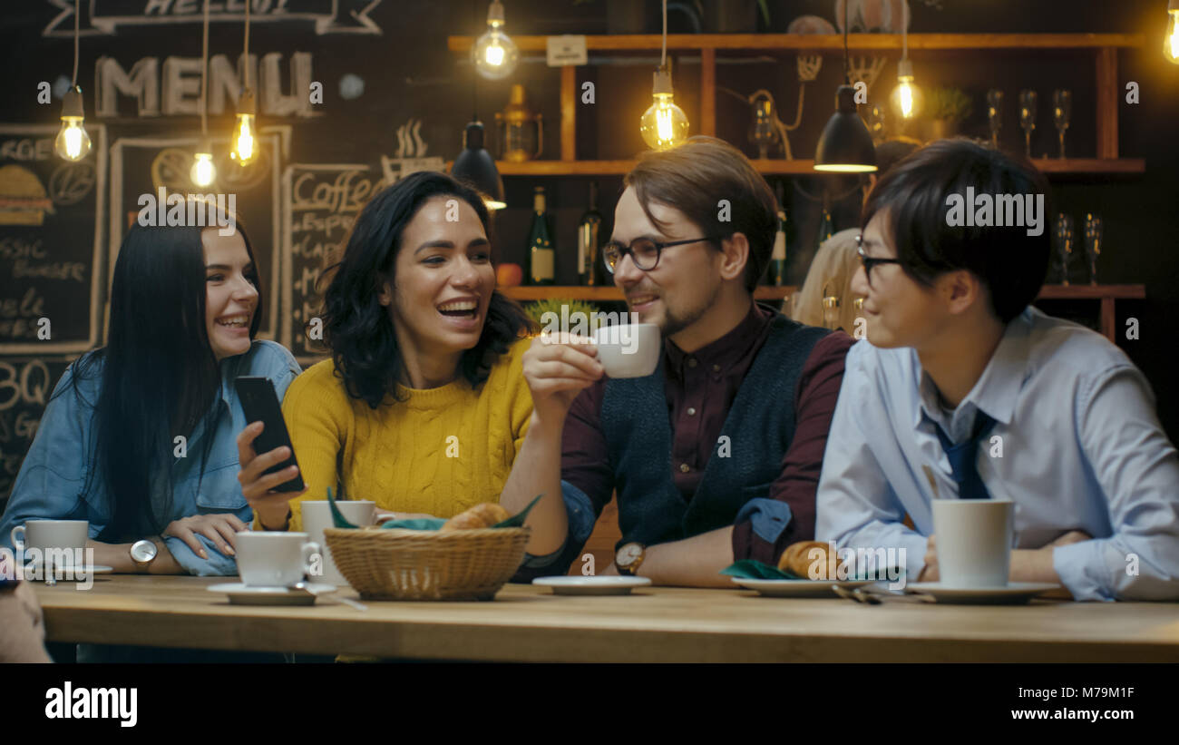 Friends Have Fun in Cafe, Drinking Hot Beverages, Talking and Sharing. Beautiful Young People in the Stylish Environment. - Stock Image