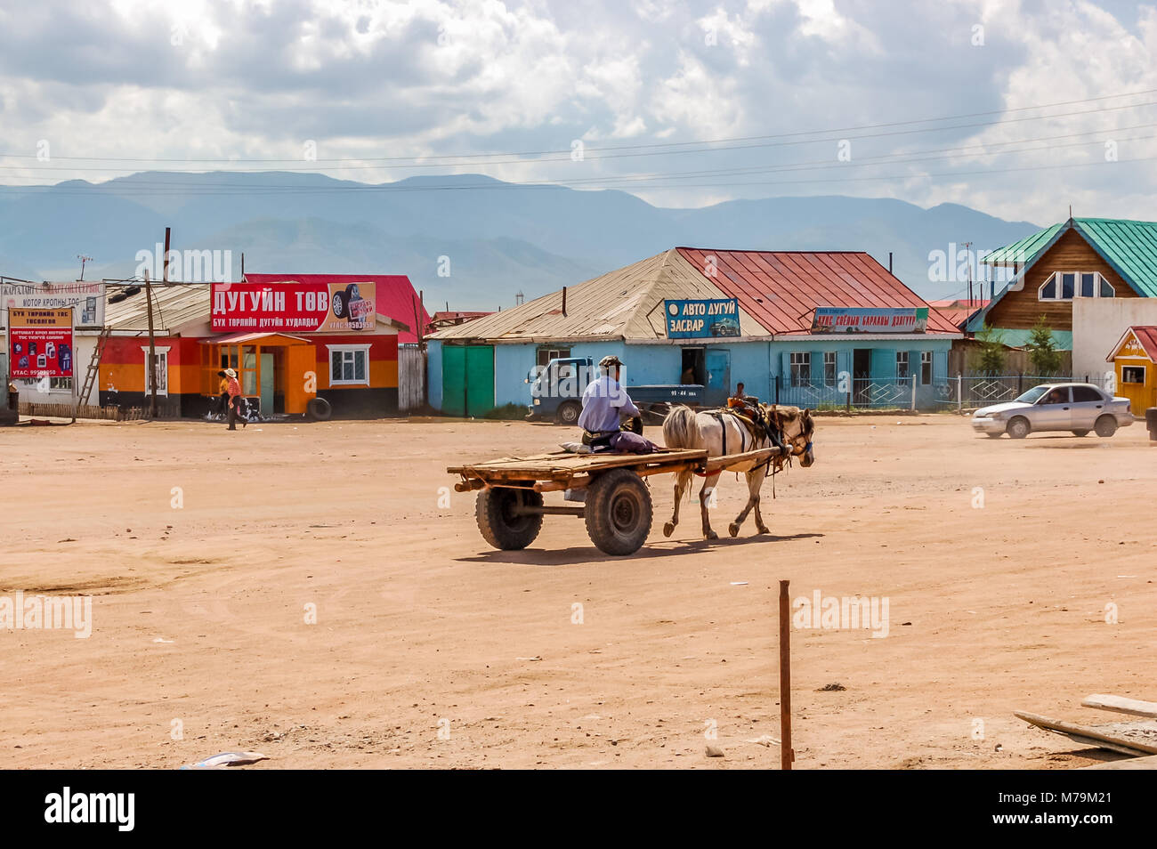 Shine-Ider District, Mongolia -  July 22, 2010: Local man drives horse & cart in tiny, remote community on steppe Stock Photo