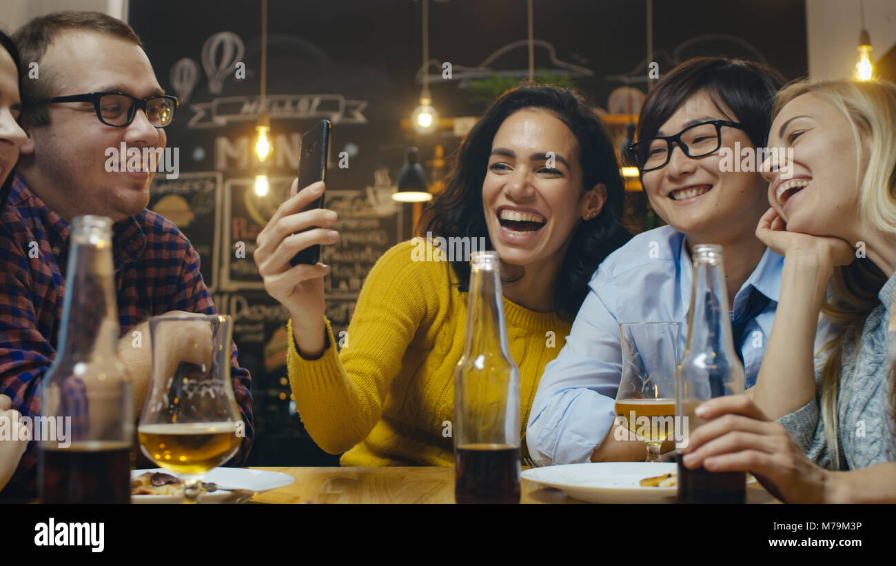 In the Bar/ Restaurant Hispanic Woman Makes Video Call with Her Friends. Group Beautiful Young People in Stylish - Stock Image