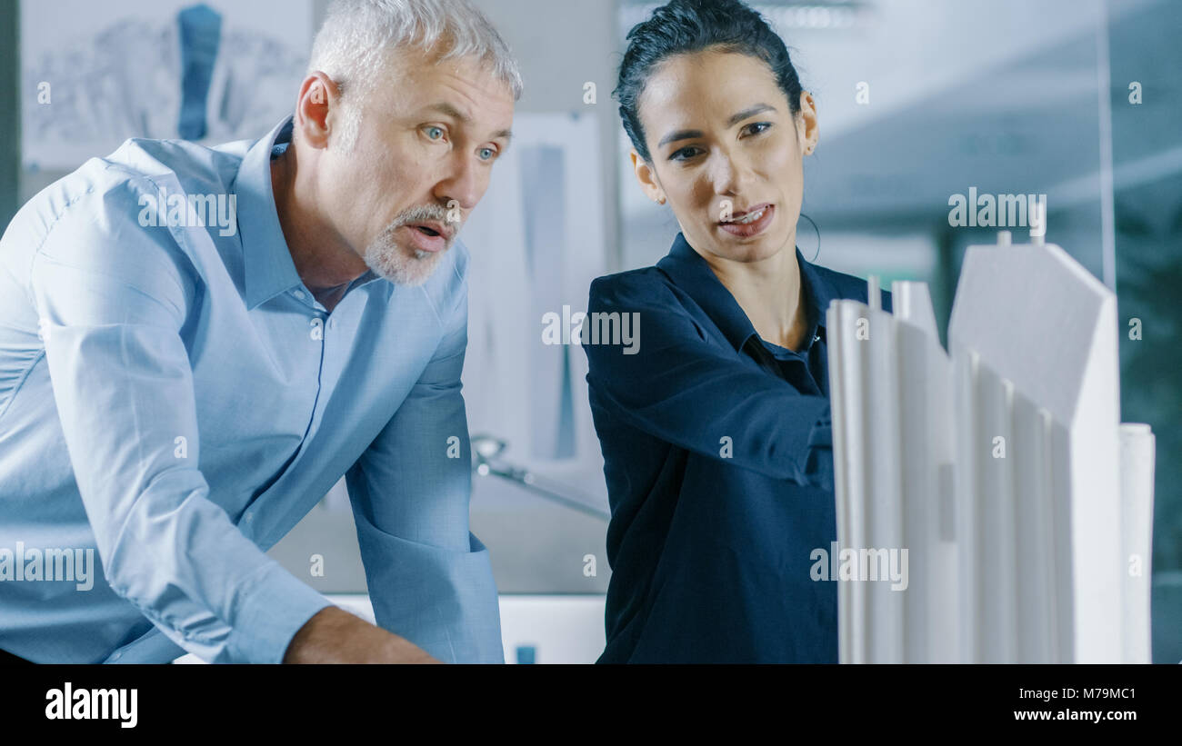 Male Senior Engineer and Female Architectural Designer Work on a Building Model Design for the Urban Planning Project. Stock Photo