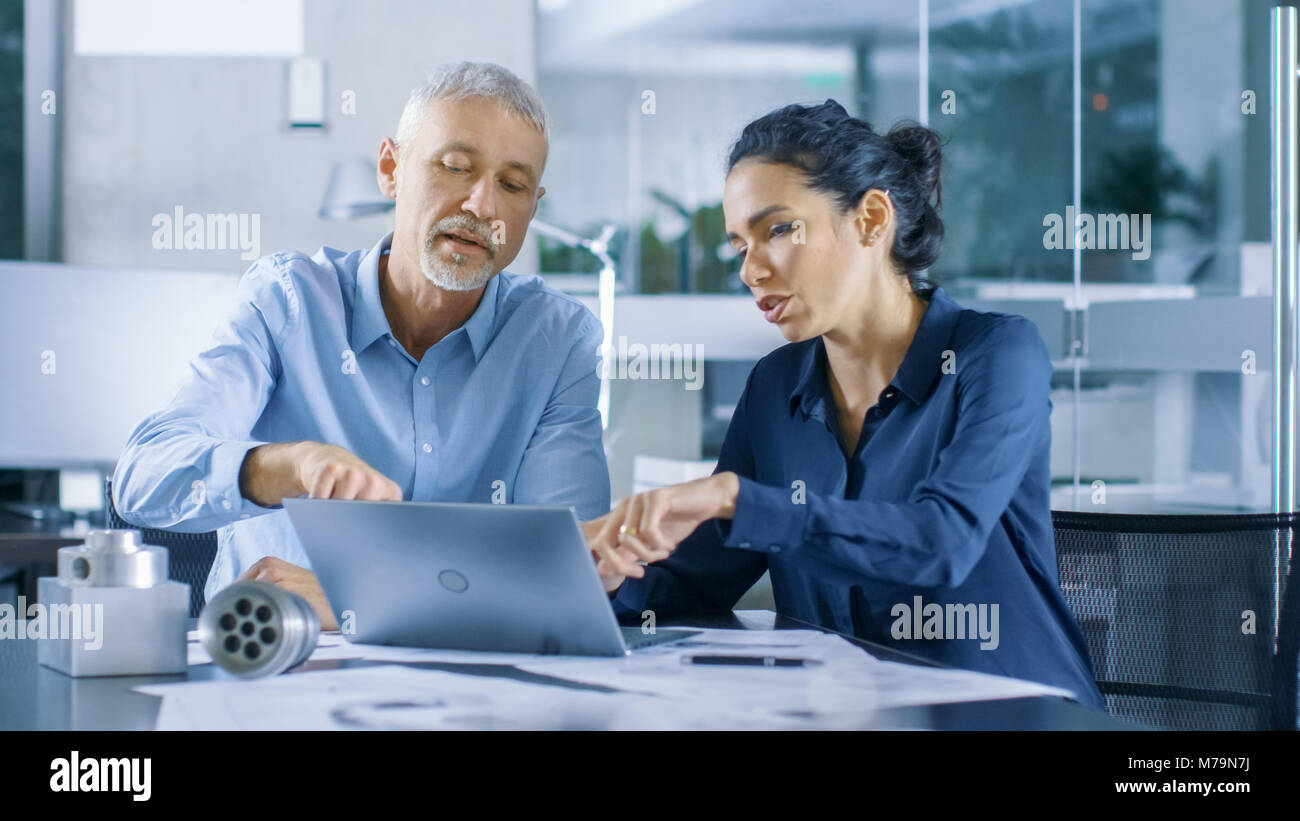 Experienced Male and Female Industrial Engineers Discuss ongoing Project while Working on a Laptop. They Design - Stock Image