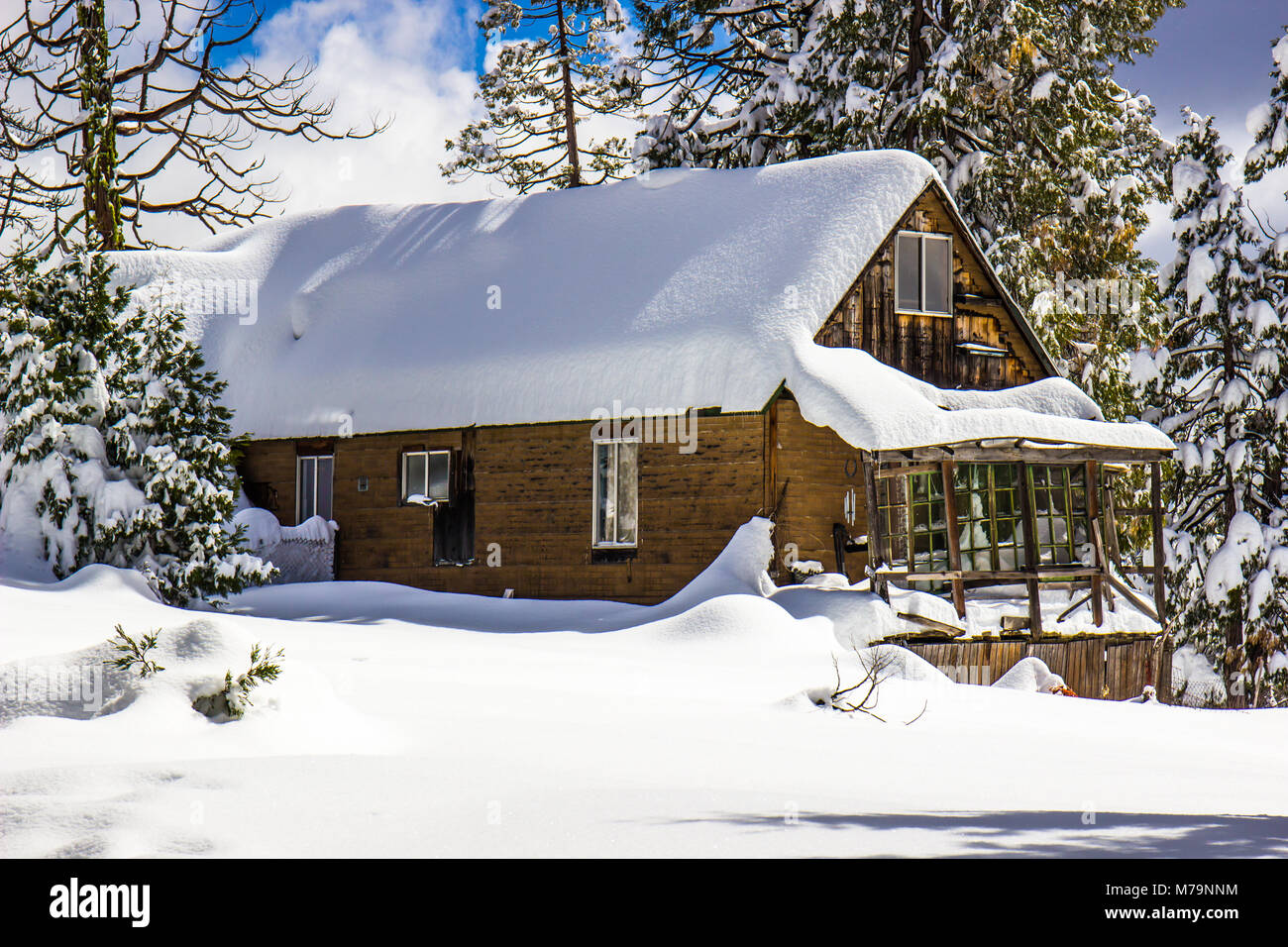Wooden Cabin With Snow Piled High On Roof Stock Photo