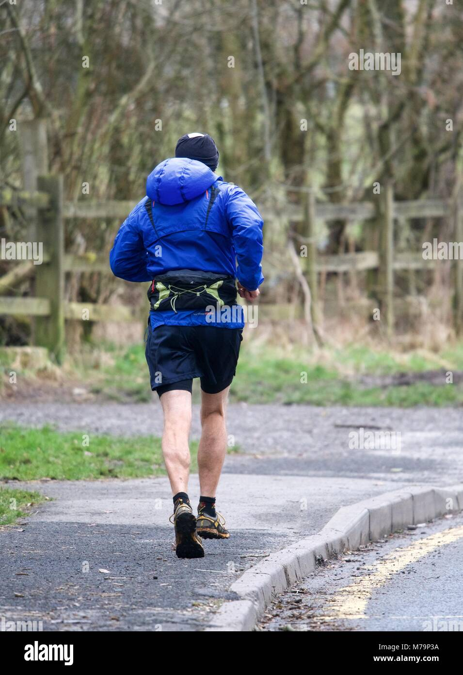 A mna jogs on the pavement in Thornsett near New Mills,  Derbyshire. - Stock Image