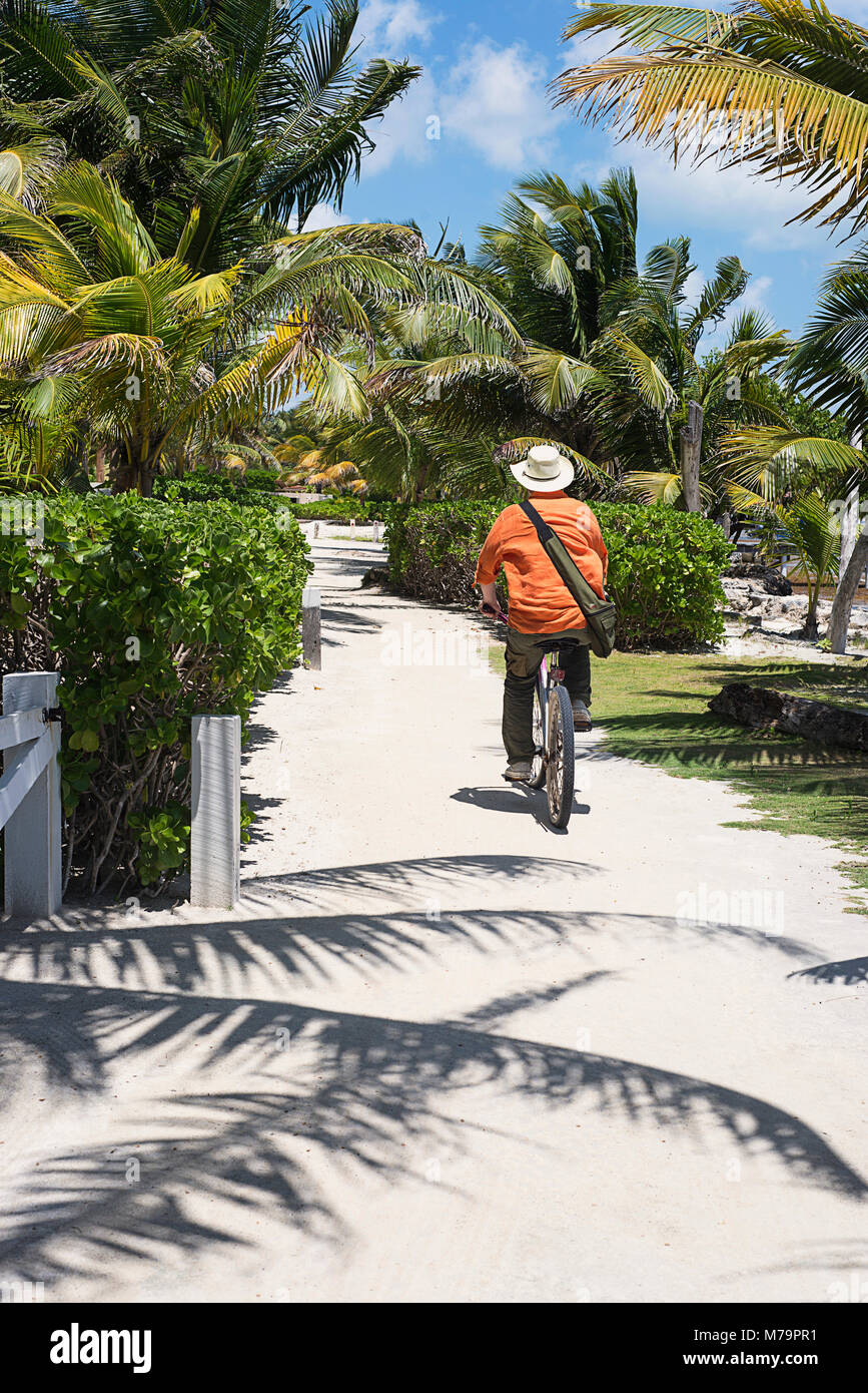 A man bicycling on a sandy path in San Pedro, Belize on the island of Ambergris. - Stock Image
