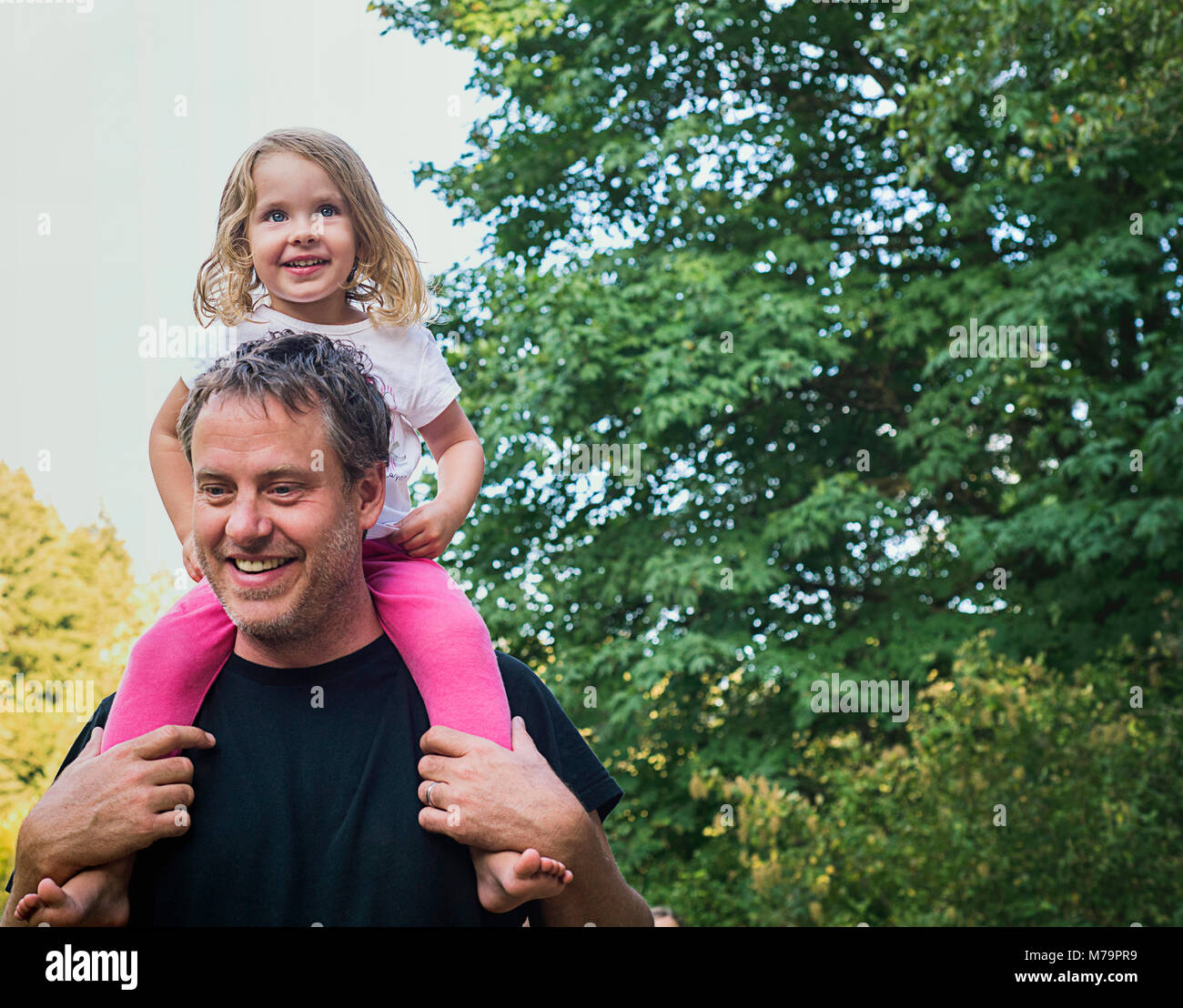 A 2 year old girl being piggy backed by her father. - Stock Image