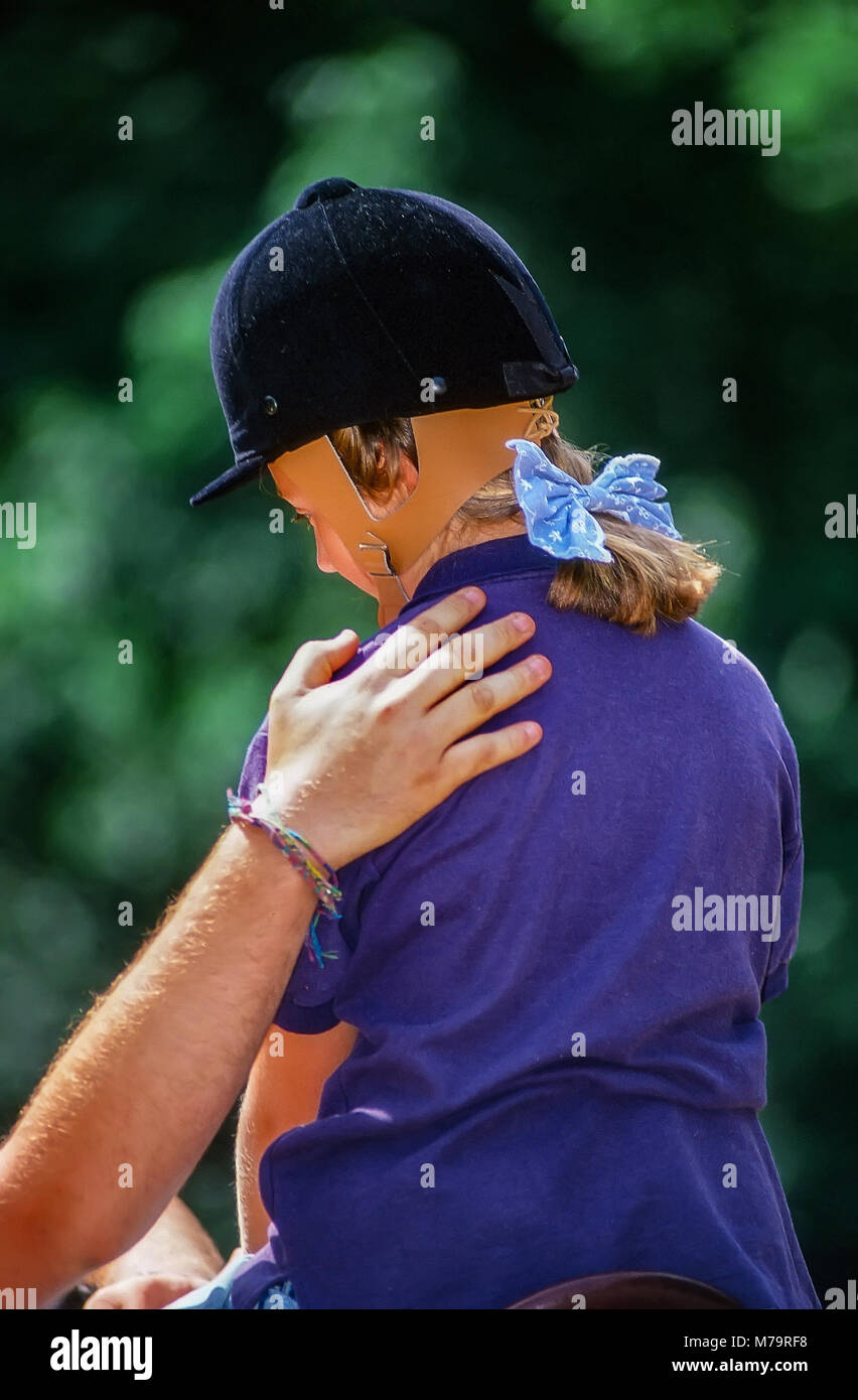A camp counselor offers a hand of encouragement to the shoulder of a young girl camper learning how to ride a horse. - Stock Image
