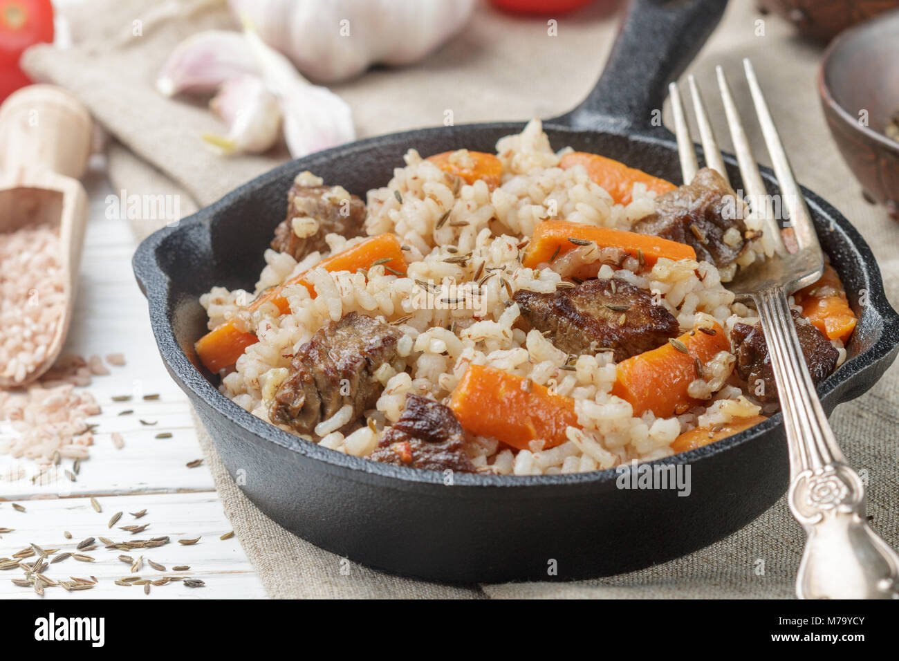 Devzira pilaf with lamb, onions, carrots and spices (cumin, coriander, pepper). Traditional dishes of Uzbek cuisine. - Stock Image